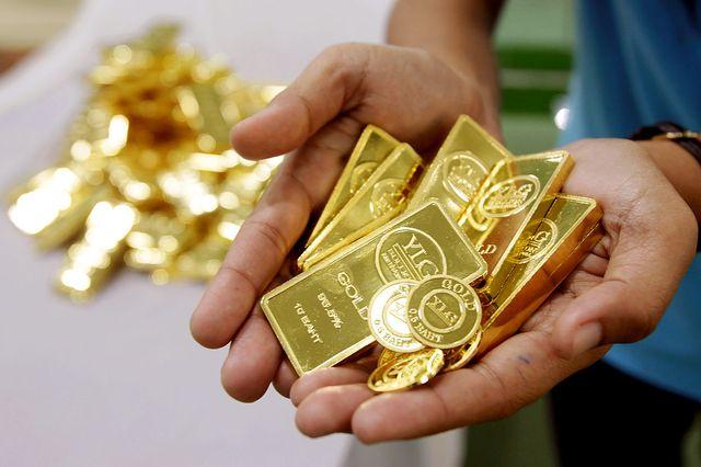 Золотые слитки в руках